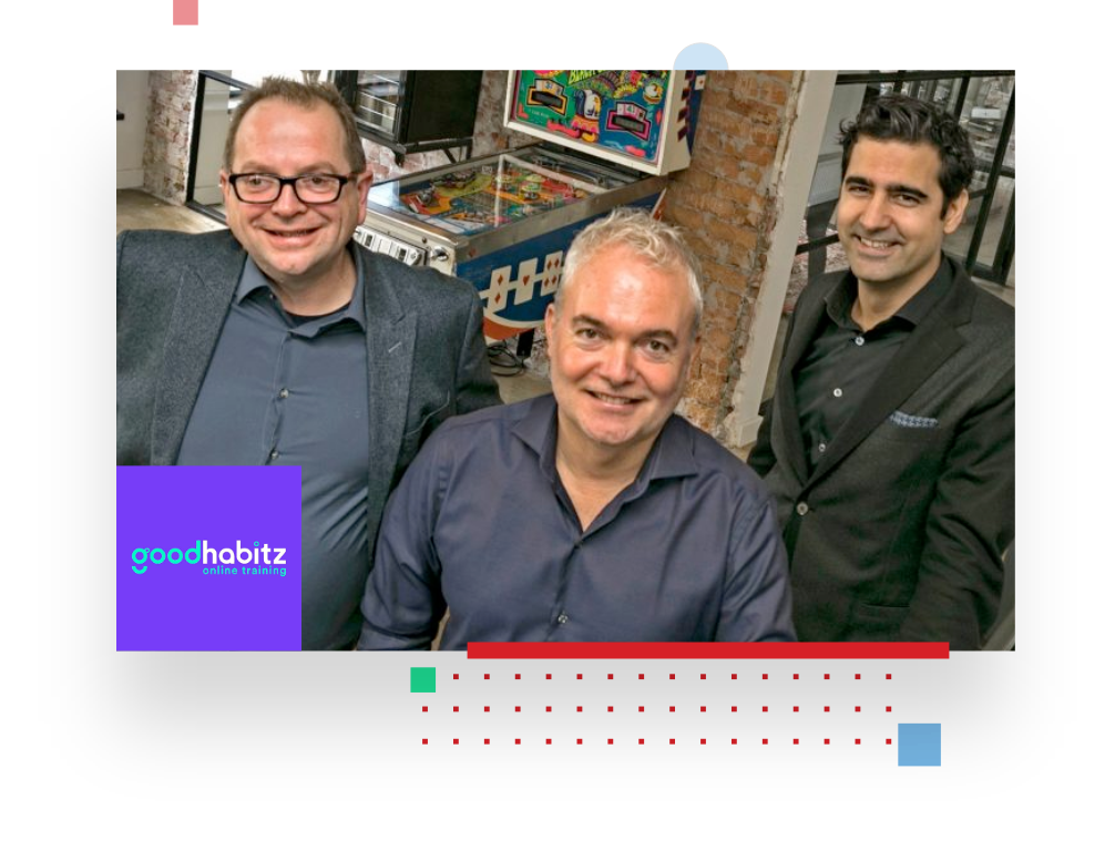 picture of three GoodHabitz employees smiling at the camera from their office, with in the background a