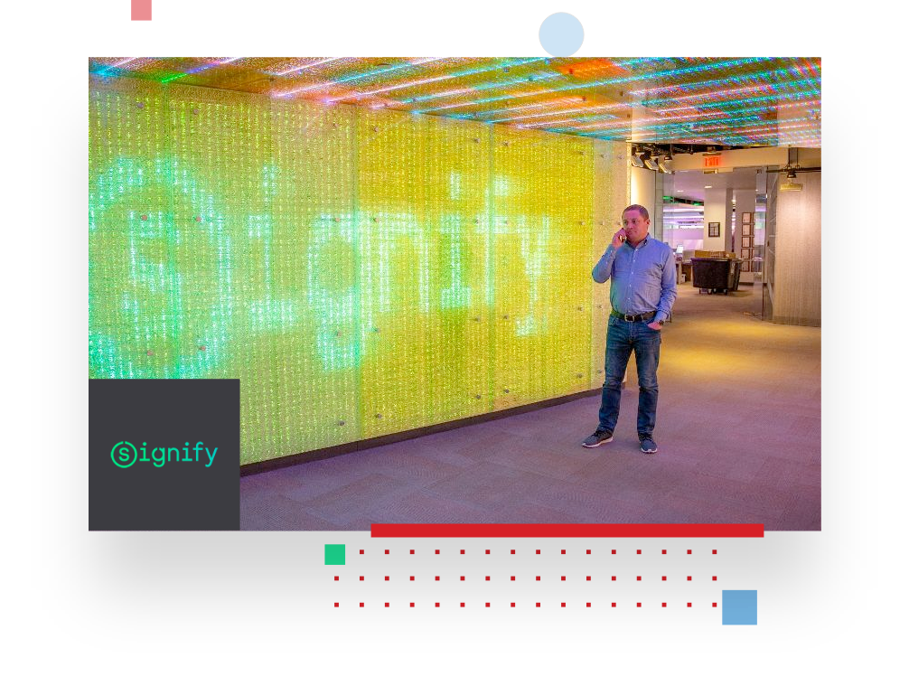 picture of a Signify employee calling on his mobile phone in front of a wall full of LED lights, displaying the Signify logo to illustrate the Signify testimonial