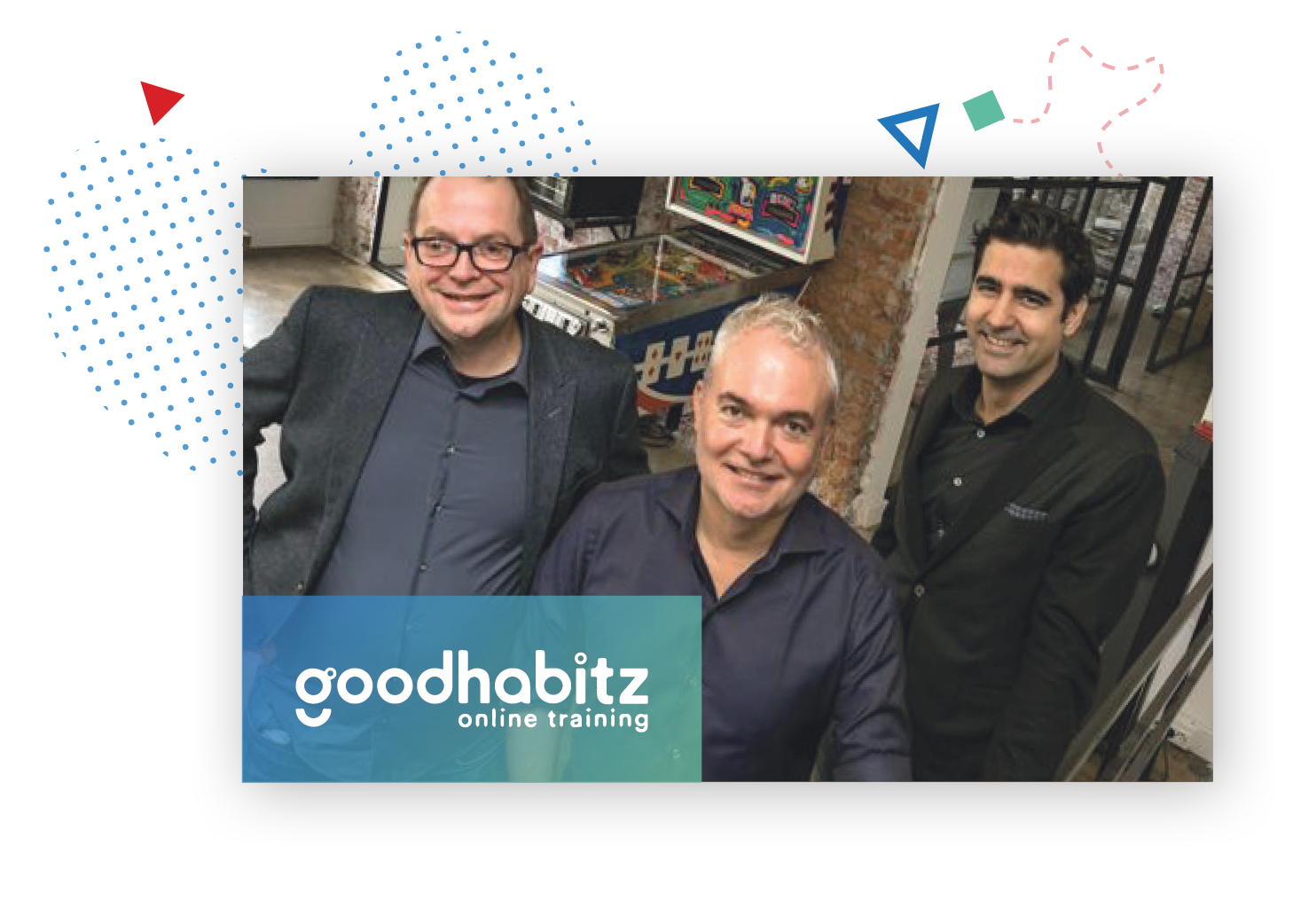picture of three GoodHabitz employees smiling at the camera from their office, with in the background a pinball machine